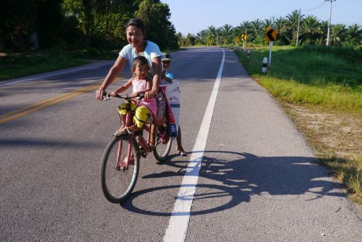 Mother and two happy children on a bike.